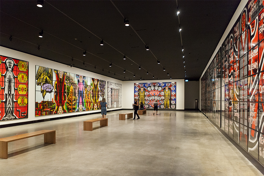 Large and colourful art exhibition with grey polished concrete floor and track lights