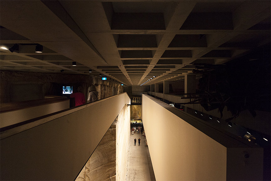 Perspective view of exhibition space at MONA is dark with exposed concrete and sandstone